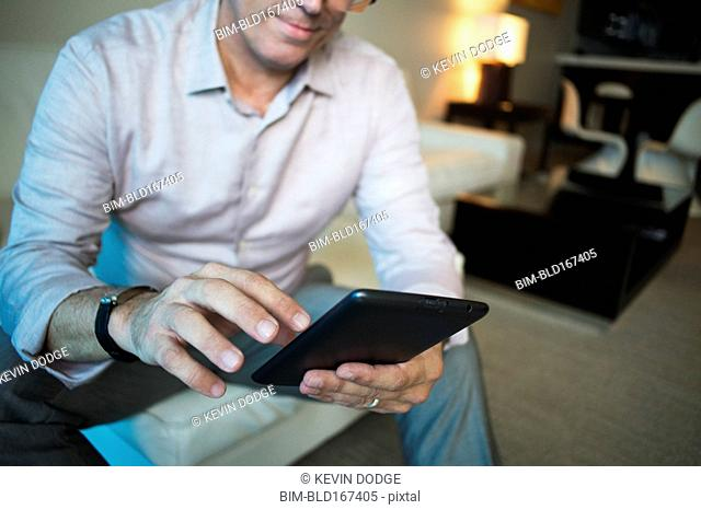 Caucasian businessman using digital tablet in hotel room