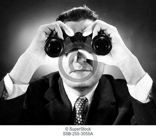 Close-up of a man looking through binoculars