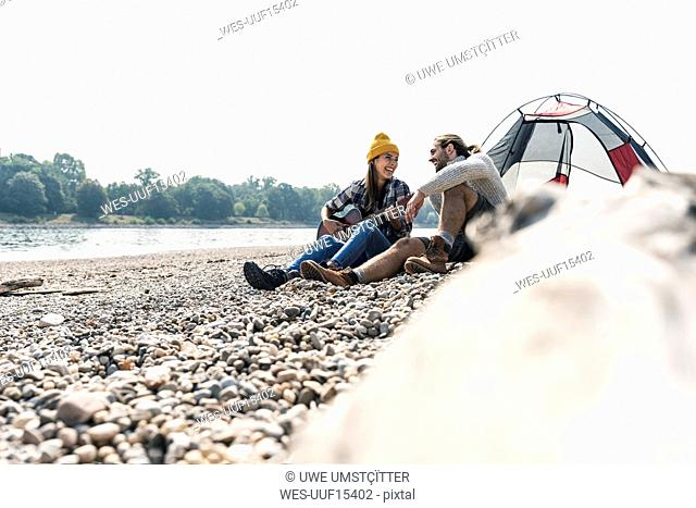 Happy young couple with guitar sitting at a tent at the riverside