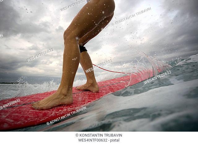Indonesia, Bali, legs of woman on surfboard