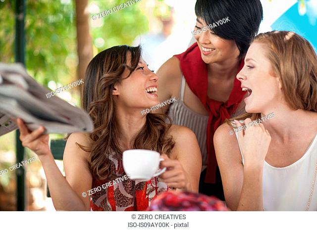 Three female friends laughing together at sidewalk cafe in city