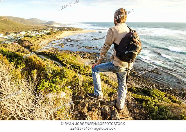 Male tourist on top of a west coast mountain range looking out to the glorious Trial Harbour, Tasmania, Australia