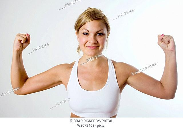 Young blond woman in workout gear happily flexes her muscles