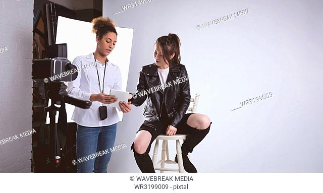 Female photographer discussing over digital tablet