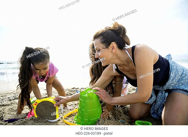 Mother and daughters making sandcastle on sunny beach