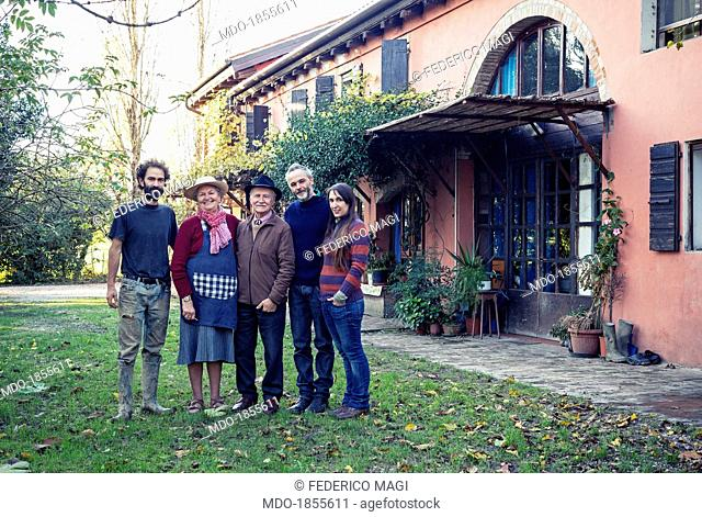 A group of people posing in the garden of the farm where they live together. Cohousing. Preganziol (Italy), November 2013