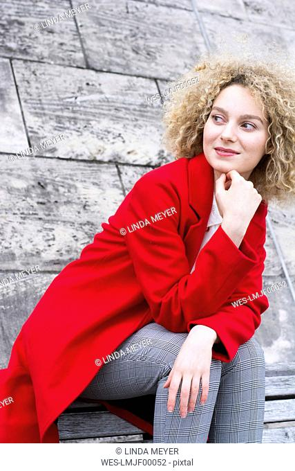 Portrait of smiling blond woman with ringlets wearing red coat watching something