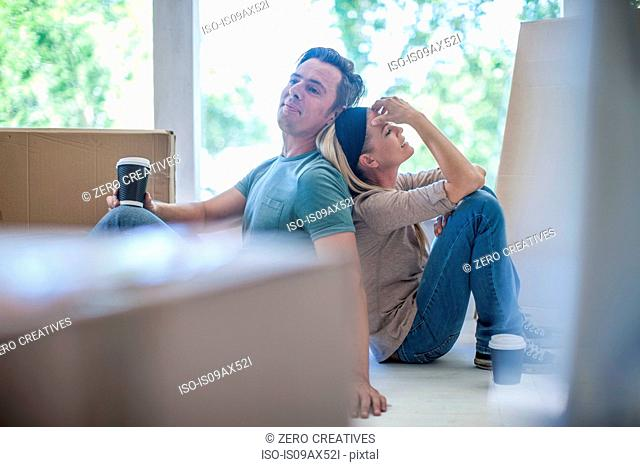 Moving house: Couple taking a break, sitting in room filled with cardboard boxes