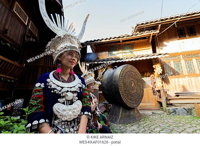 China, Guizhou, two young Miao women wearing traditional dresses and headdresses