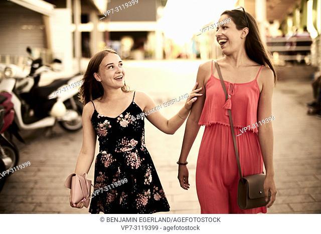 two women walking in streets of holiday destination Chersonisoss, Crete, Greece