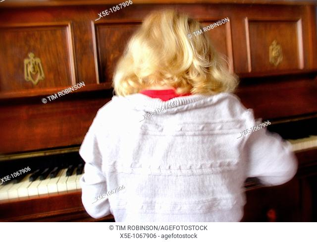 Rearview 7 year blonde girl playing piano, motion blurred