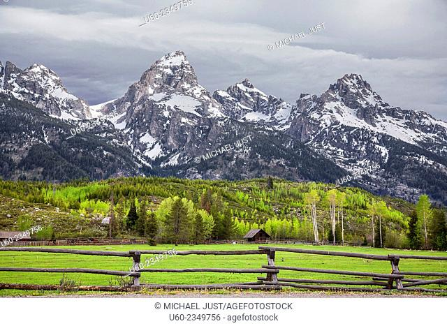 The snow-covered Grand Tetons rise sharply from the valley floor at Jackson Hole Wyoming and Grand Teton National Park