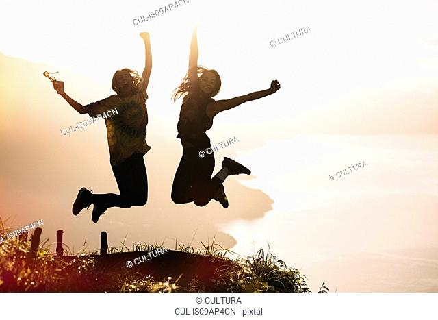 Silhouetted view of young woman and man jumping mid air at sunset above Lake Atitlan, Guatemala
