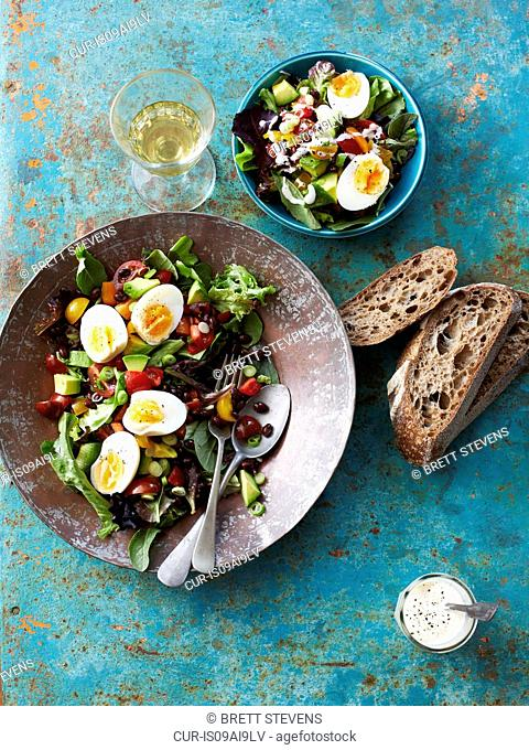 Still life of salad with boiled eggs, beans and brown bread