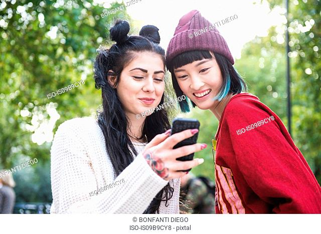 Two young stylish women looking at smartphone in city park