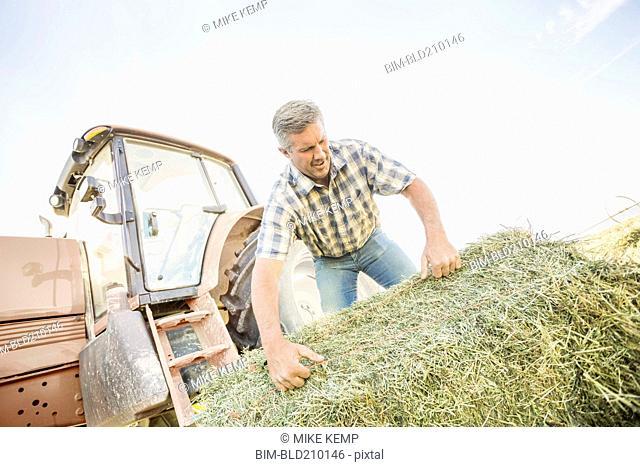 Caucasian farmer hauling hay bale