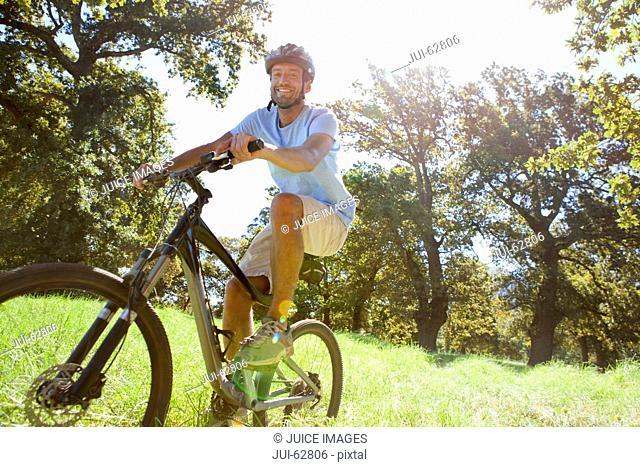 Man riding mountain bike in rural field