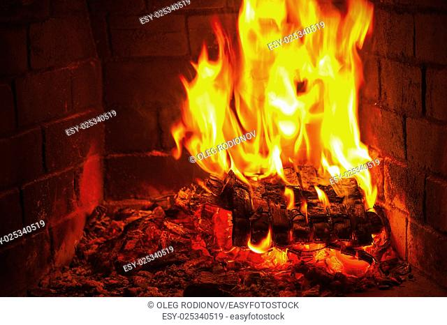 Fireplace burning. Warm burning and glowing fire in fireplace. Close up. Cozy background
