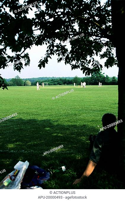 Spectator sitting under a tree watching a cricket match