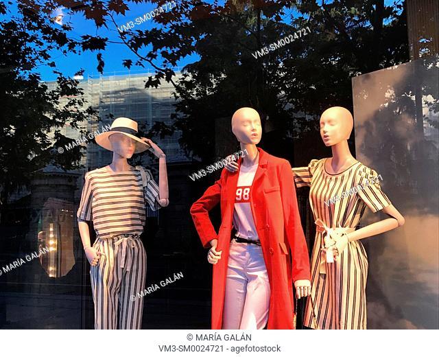 Three mannequins in a shop window. Serrano street, Madrid, Spain
