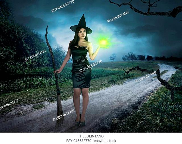 Charming halloween asian witch with magic light in his hand holding broom on countryside