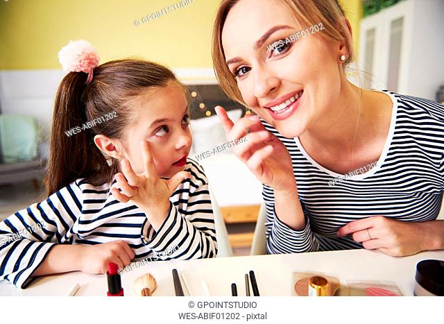 Mother and daughter applying make up together