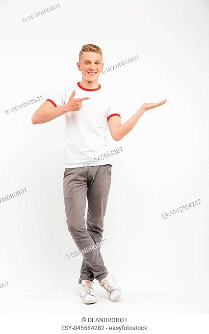 Full length portrait of a smiling teenage boy holding copy space on his palm and pointing finger isolated over white background