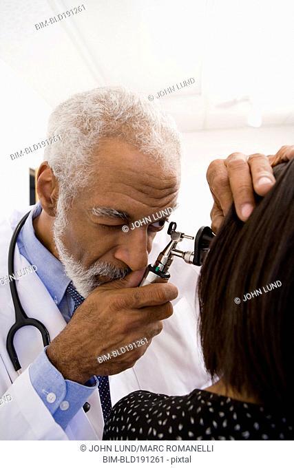 African doctor examining patient's ear