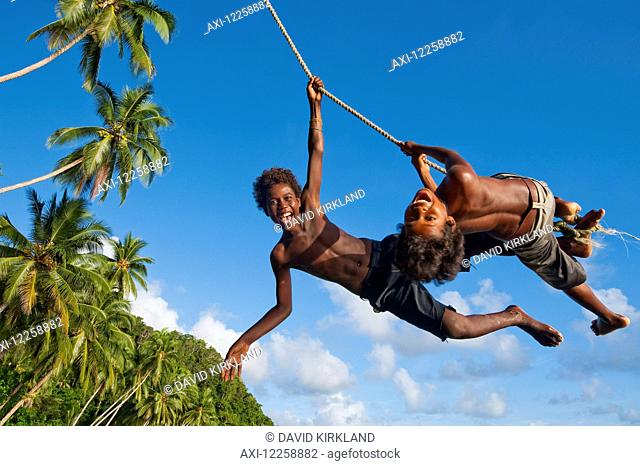 Solomon Island kids swinging from a rope; Gizo, Western Province, Solomon Islands