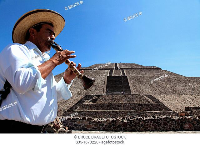 A man playing a flute in front of Pyramid of the Sun at pre-hispanic city of Teotihuacan  Teotihuacan  Mexico