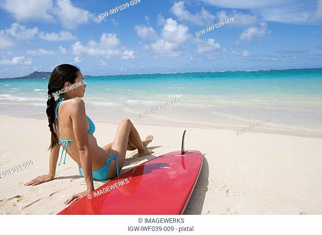 A woman sitting on beach with surfboard