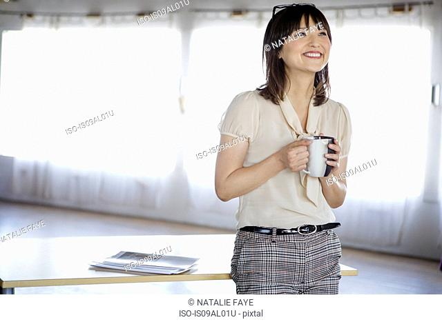 Businesswoman in office with cup