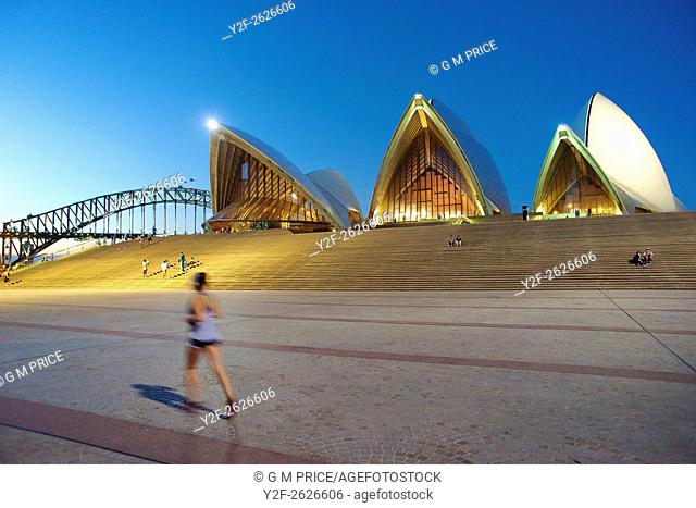 jogger and Sydney Opera House at dusk, with Harbour Bridge in the background