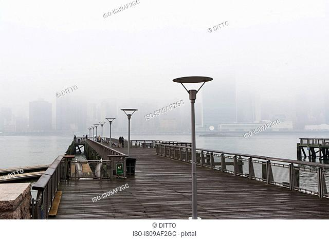 East river pier and skyline in mist, New York City, USA