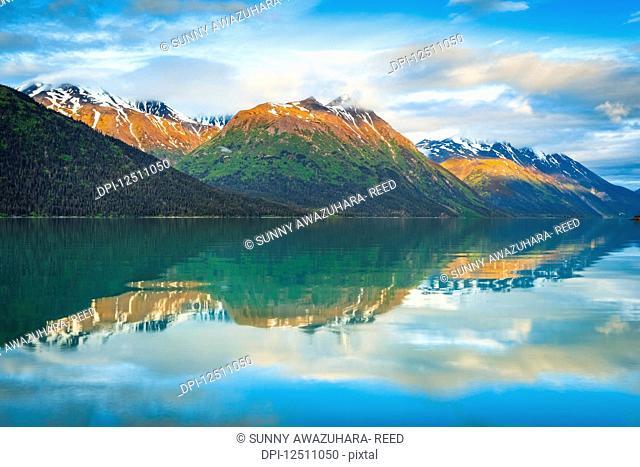 Black Mountain and Sleeping Sister Mountain in Kenai Mountains reflect on Kenai Lake at sunrise, alpenglow on the peaks. Chugach National Forest