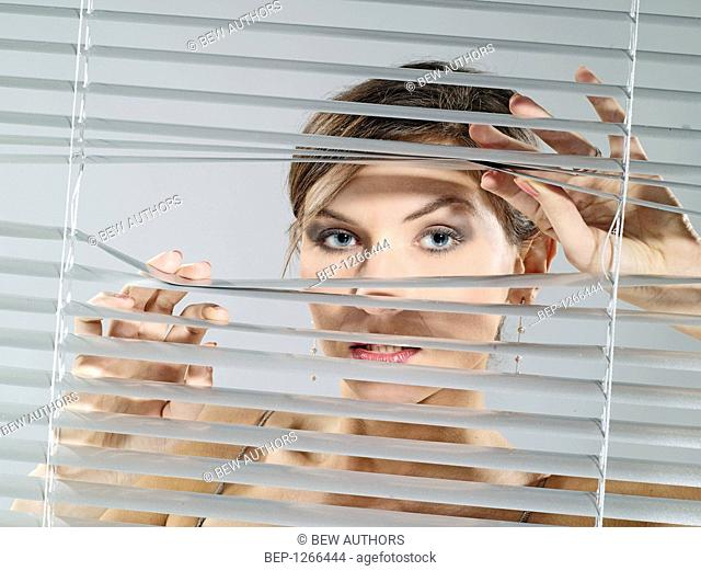 Woman's portrait while looking out the blinds