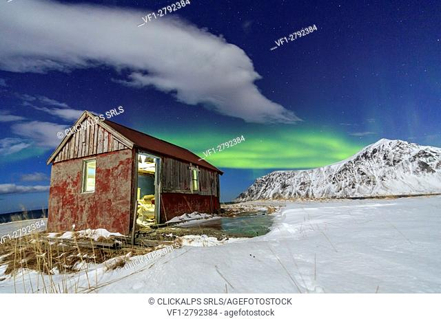 Northern Lights over an abandoned log cabin surrounded by snow and ice. Flakstad. Lofoten Islands Northern Norway Europe