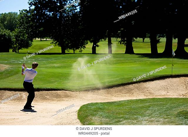 Golfer chips a difficult ball from bunker successfully to the green