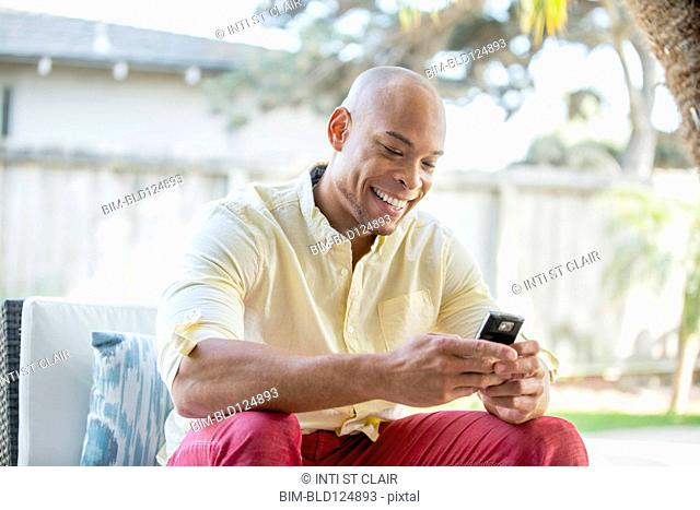Mixed race man using cell phone in backyard