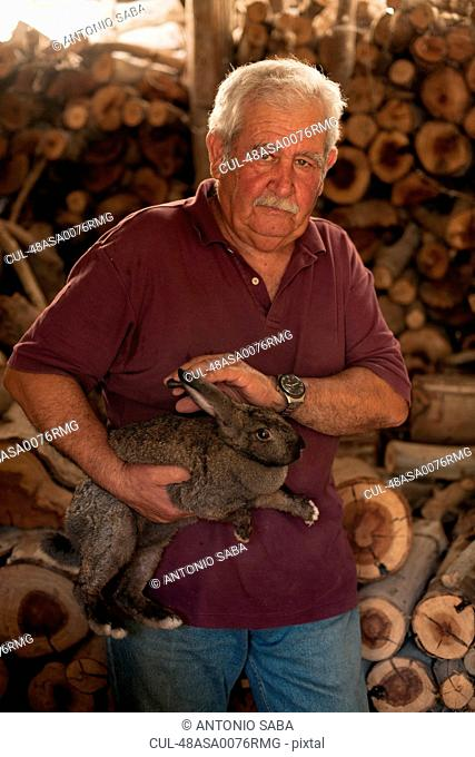 Older man petting rabbit in shed
