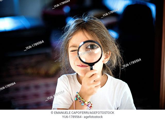 Child plays with loupe