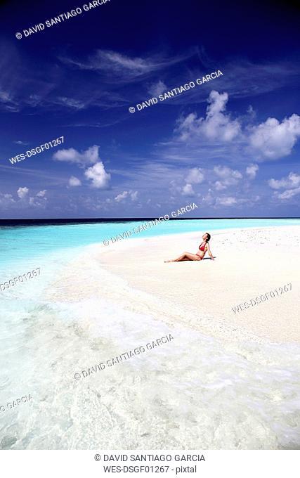 Maldives, woman sitting on beach at shallow water