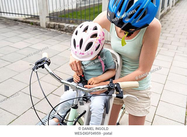 Mother and daughter riding bicycle, daughter wearing helmet sitting in children's seat, fastening seat belt