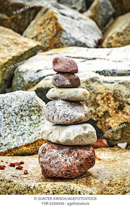 Six stones stacked on top of each other. These stacked stones are also known as Cairn