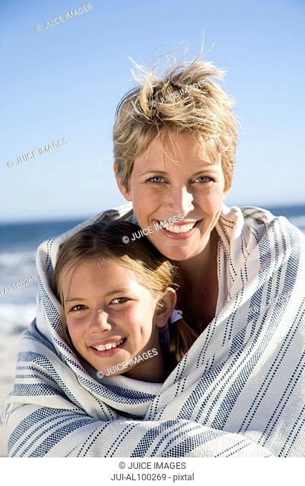 Mother and daughter in blanket on beach