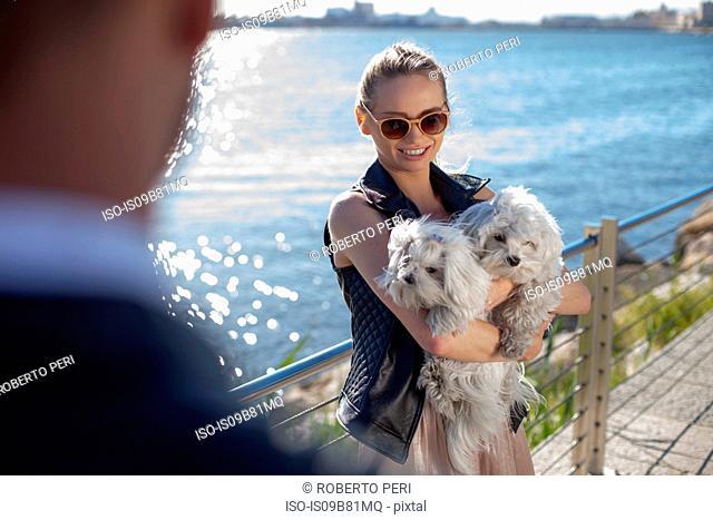 Woman holding dogs on riverbank, Cagliari, Sardinia, Italy, Europe
