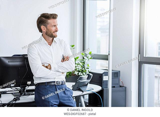 Portrait of smiling businessman with arms crossed in the office