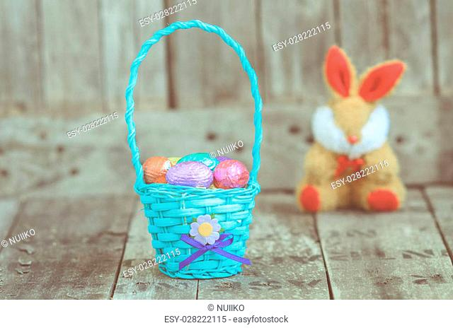 chocolate easter eggs in a basket and rabbit doll on wooden background. Vintage toned