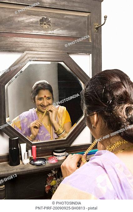 Woman getting shy in front of a mirror