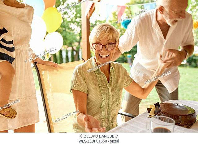 Exuberant senior couple on a garden party